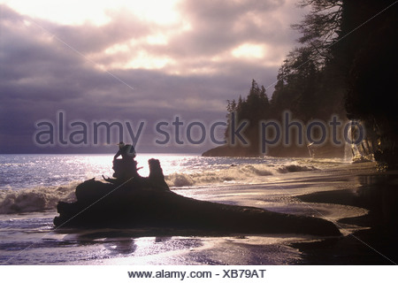 Person sitting on a log watching a storm roll inat Mystic Beach on the Juan de Fuca marine trail, British Columbia, Canada. - Stock Photo