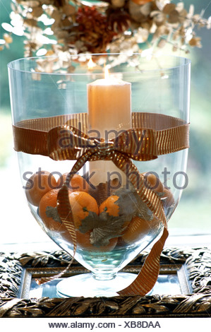 Decorating Gold at Christmas Large glass vase filled oranges, gold leaves and lit candle Wide gold ribbon tied in a bow around - Stock Photo