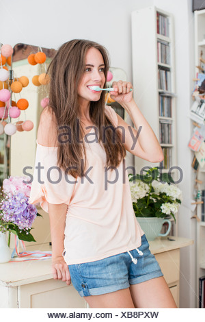 Smiling woman brushing her teeth - Stock Photo