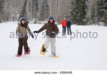 Two young girls race across Pyramid lake in snowshoes as parents look on, in Jasper National Park, near Jasper, Alberta Canada - Stock Photo