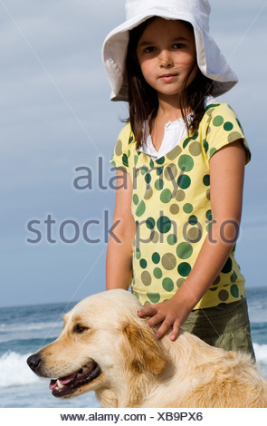 Girl 6 8 in sun hat standing on beach with dog smiling side view portrait - Stock Photo