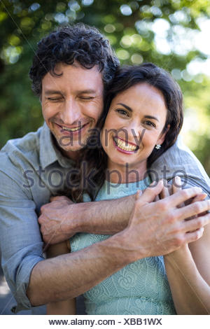 Portrait of smiling wife being hugged by husband - Stock Photo
