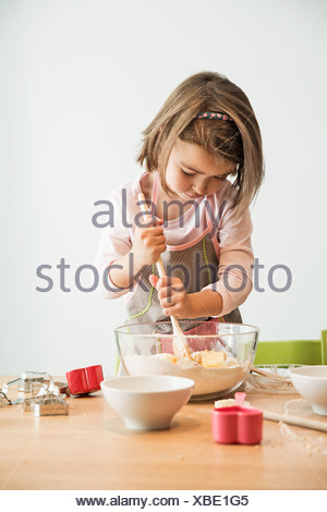 Girl mixing batter in bowl - Stock Photo