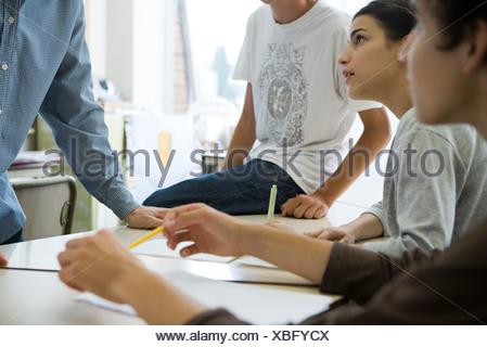 High school students, teacher in casual classroom conversation - Stock Photo
