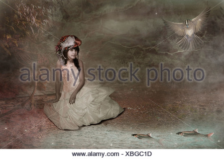 young woman sitting by a pond wearing old fashioned dress - Stock Photo