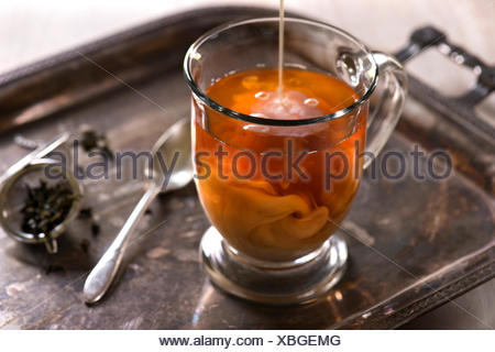 A glass of tea with milk pouring in and swirling. Antique, rustic styling with light background. - Stock Photo