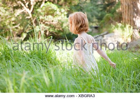 Little girl in field of grass - Stock Photo