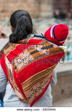 A Woman Carries A Baby On Her Back; Cusco Peru - Stock Photo