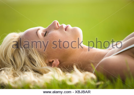Young woman lying in the grass - Stock Photo