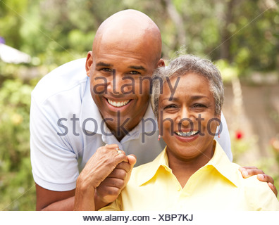 Senior Woman Being Hugged By Adult Son - Stock Photo