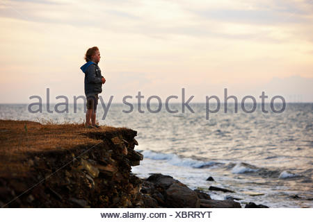 Boy on a cliff by the sea, Sweden. - Stock Photo