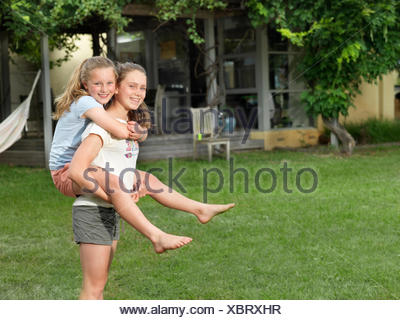 Teenage girl giving her sister piggyback ride in garden - Stock Photo