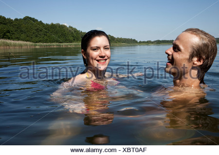 Man and woman happily swimming in lake - Stock Photo