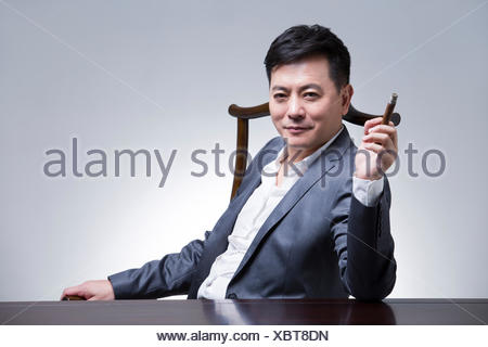 Mature businessman with cigar - Stock Photo