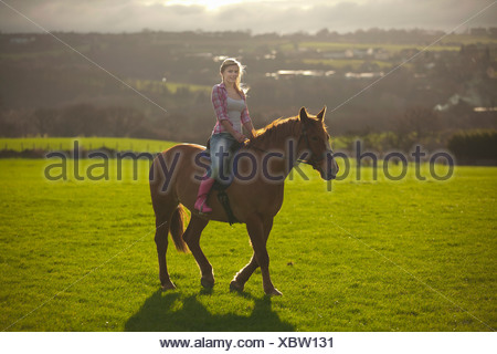 Teenage girl riding horse in field - Stock Photo