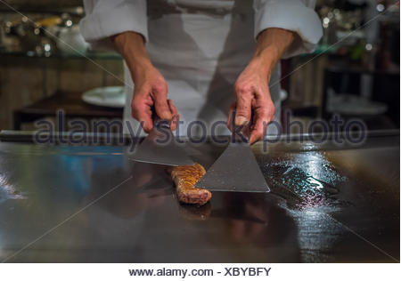 Chef cooking wagyu beef in Japanese teppanyaki restaurant, Tokyo, very shallow focus - Stock Photo