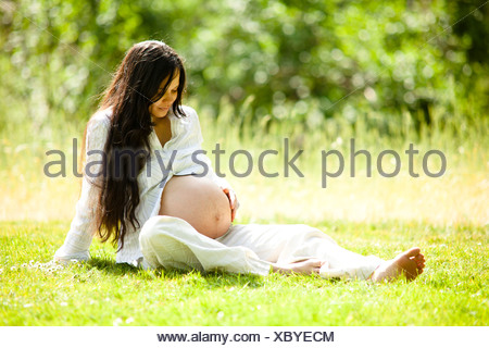 Pregnant woman sitting in meadow - Stock Photo