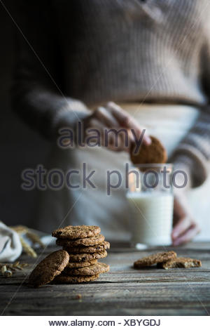 Cereal biscuits on wooden table and woman dipping a biscuit in a glass of milk - Stock Photo