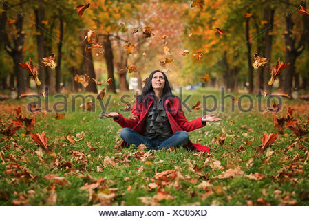 Woman sitting on grass throwing leaves in the air - Stock Photo