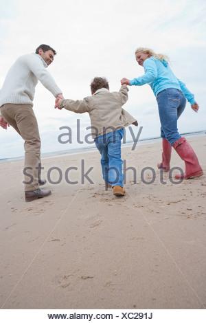 Family Running Along Winter Beach - Stock Photo