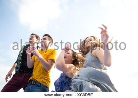 Group of young adults, running, outdoors, low angle view - Stock Photo