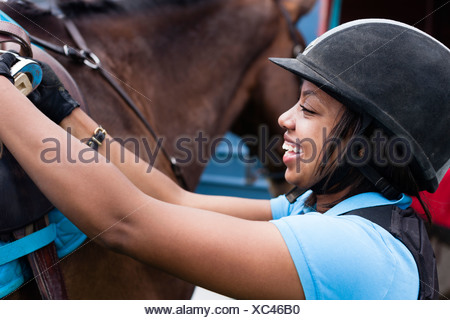 Close up of young woman putting saddle on horse - Stock Photo