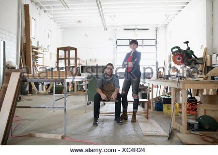 Portrait confident, serious carpenters in workshop - Stock Photo