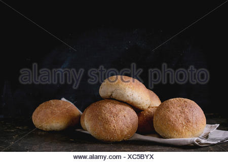 Fresh baked wholegrain buns on gray kitchen towel over dark table with black background. - Stock Photo