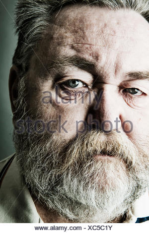 Portrait of senior man with full beard, close-up - Stock Photo