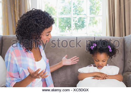 Pretty mother scolding her daughter on the couch - Stock Photo