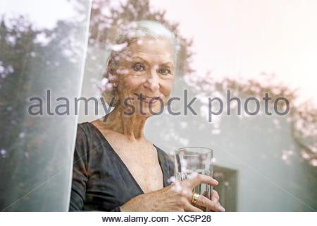 View through window of senior woman holding tumbler looking at camera smiling - Stock Photo