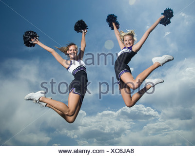 Cheerleaders with pom poms jumping - Stock Photo