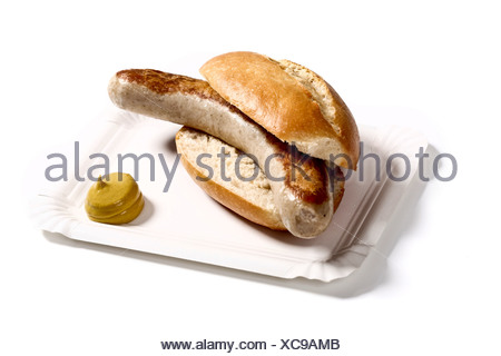 Bratwurst sausage in a bun with mustard on a paper plate - Stock Photo