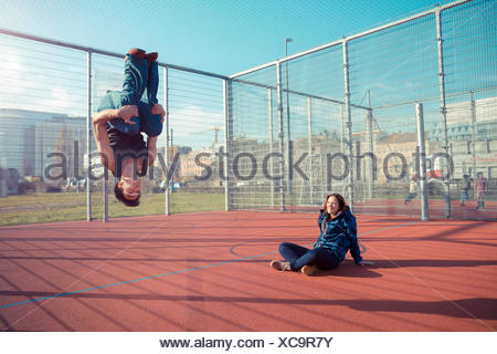 Young man on sports field doing a somersault - Stock Photo