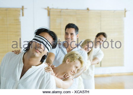 Group therapy, standing in single file line with hands on each other's shoulders - Stock Photo