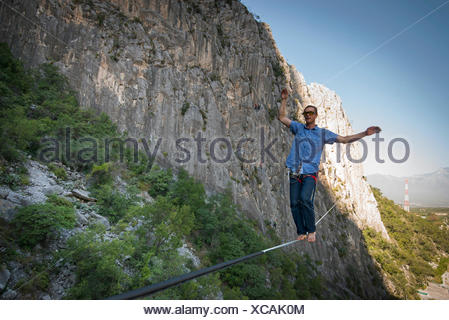 Adventurous man slacklining between two rock walls at El Portero Chico, Monterrey, Mexico - Stock Photo