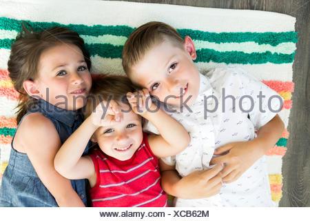 Portrait of siblings (2-3, 6-7) lying on carpet - Stock Photo
