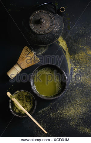 Green tea matcha powder and hot drink in black bowls standing with iron teapot, bamboo traditional tools spoon and whisk over dark metal background. T - Stock Photo