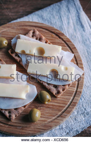 Ham and cheese crisp bread sandwiches and olives served on a wooden cutting board - Stock Photo