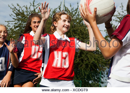 Schoolgirl netball players defending - Stock Photo