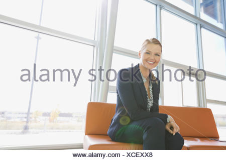 Portrait of businesswoman sitting in office lobby - Stock Photo
