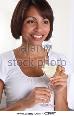 WOMAN HOLDING A GLASS OF WHITE WINE - Stock Photo