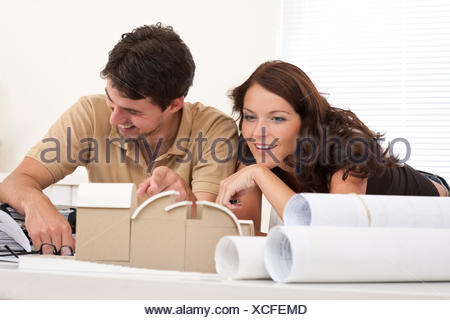 Smiling man and woman with architectural model - Stock Photo