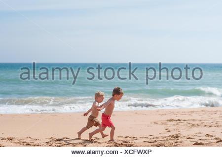 Two boys running along the beach - Stock Photo
