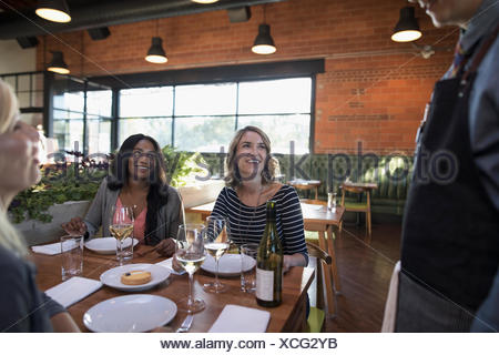 Smiling women friends dining, drinking wine and talking to server at restaurant table - Stock Photo