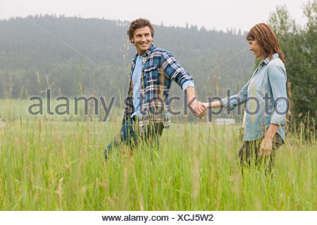 middle-aged couple walking in high grass holding hands - Stock Photo