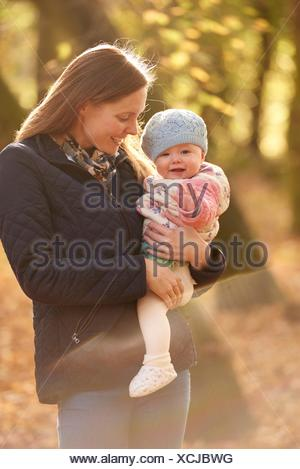 Portrait of mid adult woman and baby daughter in autumn park - Stock Photo