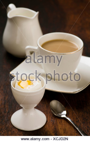 coffee with milk and boiled egg in eggcup - Stock Photo