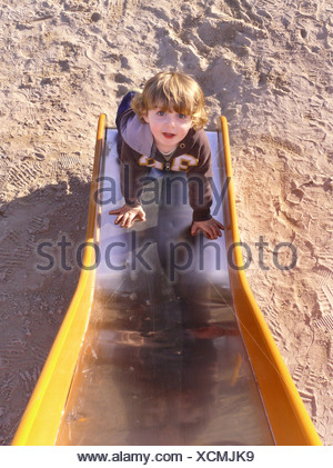 little boy climbing a slice on a playground - Stock Photo