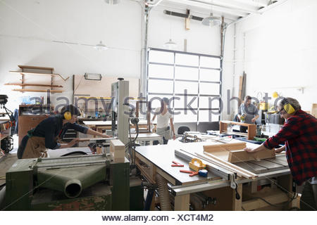 Carpenters cutting wood, using table saws in workshop - Stock Photo